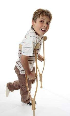 A boy with sprained injured ankle using crutches for support.  He is looking up and smiling.For healthcare and insurance themes photo