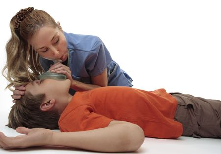 Female nurse using a resuscitation mask on a young unconscious boy.  Focus to boy.