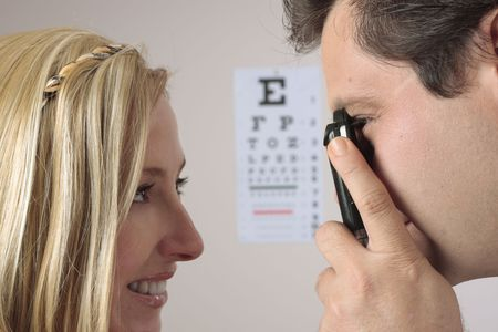 Closeup of a an optometrist eye doctor checking a female patient eyes.  Focus to man.