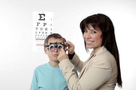 An optometrist putting trial frames on a child.  She is looking around and smiling. photo