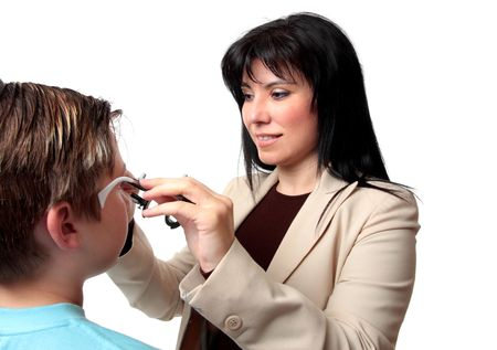 An optometrist puts trial frames on a patient photo