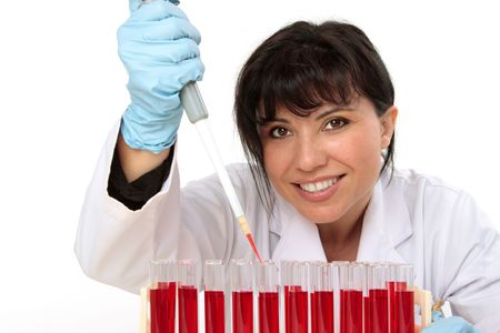 Female biologist, hematologist, holding a manual pipette with sample from test tubes. Stock Photo