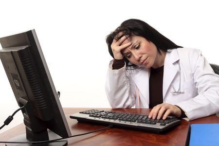 exasperated: Overworked tired or stressed doctor sitting at computer.