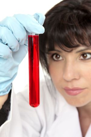 pathologist: Closeup of woman holding a  test tube and looking intently.  Focus to test tube.