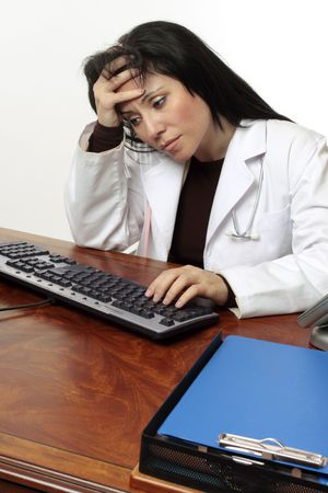 Tired or stressed doctor with head in hands sitting at computer. Stock Photo