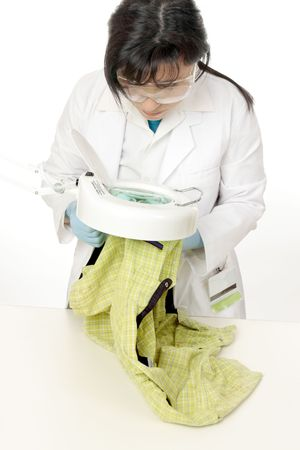 residue: a forensic scientist examines evidence under a magnifying lamp.  Collection samples can  include skin, hair, blood, dirt, fibres, gunshot residue,   etc...