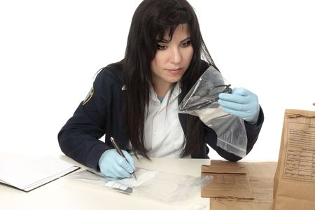 criminal act: A detective with evidence from a crime scene.  Properly collected and preserved evidence can establish a strong link between an individual and a criminal act. Stock Photo