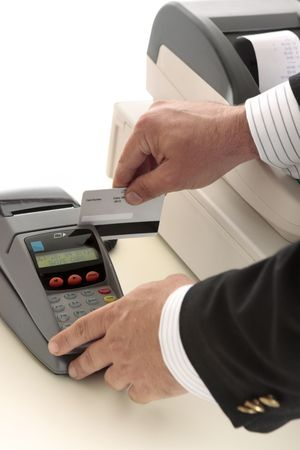 eftpos: A salesman retailer swipes a credit or debit card through a pos terminal.  Focus to terminal and card.  Details removed from card. Stock Photo