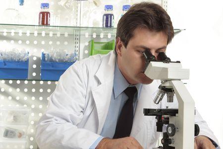 Un investigador observa una sustancia en una diapositiva en virtud de un est�reo microscopio Foto de archivo - 3772881