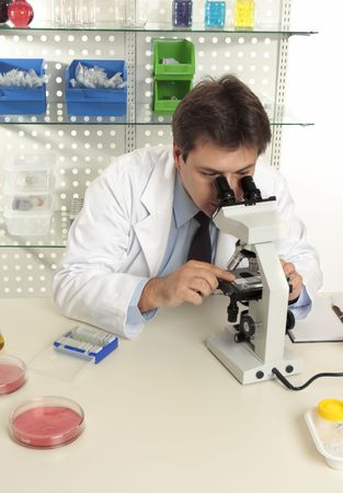magnification: A scientist observes an object under magnification of a microscope in the laboratory