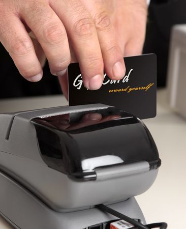 debit card: Man swiping a gift card, credit or debit card.   Original card front has been replaced including text with my own.   Focus to hand and card.  Shallow dof.  This could be a sales person or a customer.  You could also replace this with your own store card o Stock Photo