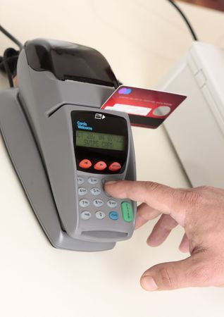 pos: A retailer, salesman or customer using an eft pos machine to make a transaction payment.  Focus to hand and machine only.