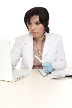 A forensic investigator with evidence swab, computer and notes. photo
