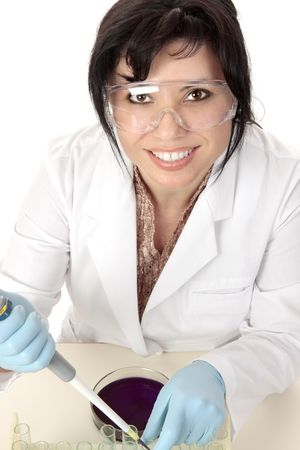 Smiling medical or scientific researcher sitting at desk with pipette and petri dish. photo
