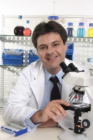 Smiling Scientific researcher sitting at laboratory desk  using a microscope for further analaysis of substances...