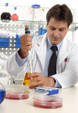 A male scientist, pharmacist or researcher using a pipette to take a sample fluid from erlenmeyer flask in a laboratory. photo