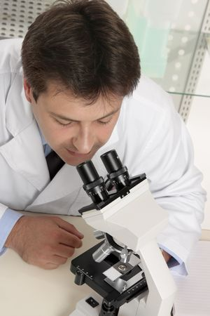 A research scientist looking through a stereo microscope to view a prepared slide. photo