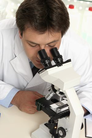 observes: A scientist observes substance through microscope