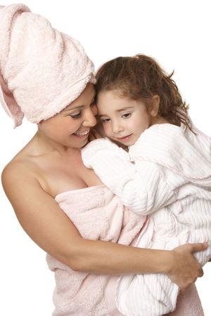 showering: Caring nurturing mother cuddles her daughter at bathtime