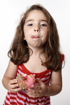 A little girl in a red striped dress is  holding a pink iced doughnut and licking her lips with satisfaction.