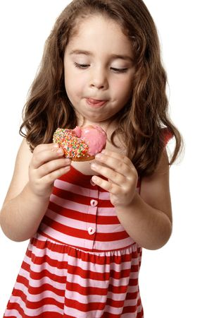 Young girl eating a delicious pink iced doughnut.  She is looking down at it  and licking her lips. Stock Photo - 4402616