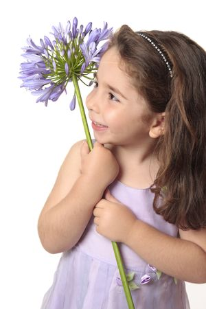 Pretty little  girl in purple mauve dress holding a beautiful agapanthus flower and smiling sweetly. photo