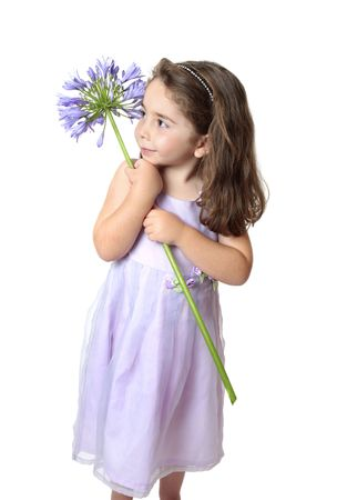 Pretty young girl in a dress holding a large purple agapanthus. photo