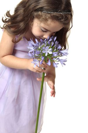A young girl smelling a large agrican lily - agapanthus photo