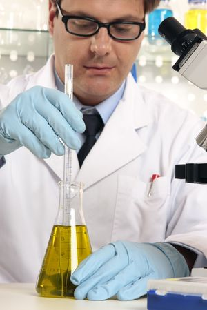 stirrer: Scientist using a stirrer to mix liquids in flask.  Focus to hands and science labware. Stock Photo