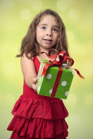 Pretty little girl with arms outstretched, giving at present. photo