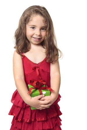 sweetly: Little girl in a red dress holds a green and red present and smiles sweetly.