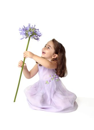 purple dress: A little girl sitting on the floor in pretty mauve dress decorated with floral appliques, is spinning a large stemmed agapanthus lily flower in bloom, with much delight and excitement.