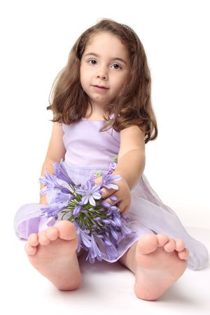 A young toddler girl wearing a pretty dress and sitting on the floor with a large agapanthus flower photo
