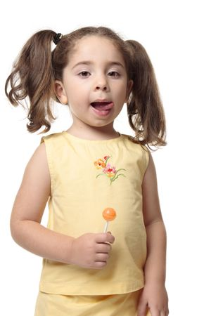 A little girl licks her lips.  She iis wearing a yellow outfit with hair in ponytails and she is holding a candy lollipop photo