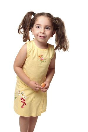Cute toddler girl with natural wavy hair pulled into ponytails.  She is wearing a yellow outfit with embroidery and is holding a lollipop candy on a stick. Stock Photo - 4902068
