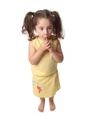 sucking lollipop: A small preschool girl eating a sweet lollipop.  She is barefoot and wearing a skirt and top with hair in ponytails. Stock Photo