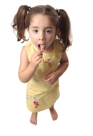 A little girl sucking on a lollipop candy.  She is dressed in a yellow outfit and has her hair in ponytails. Stock Photo - 5093715