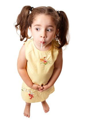 A small cute girl with hair in ponytails is sucking on a lollipop sweet.   She is standing on a white background and looking sideways.  Space for copy. Stock Photo - 5147689