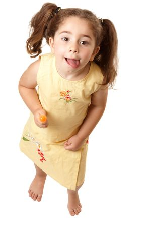 full lips: Above view of a young girl child standing  and licking her lips.    Stock Photo