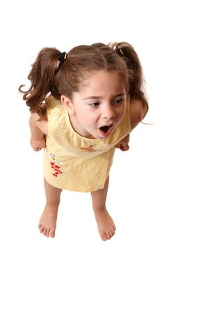 A young little girl with fists clenched screams or throws a tantrum