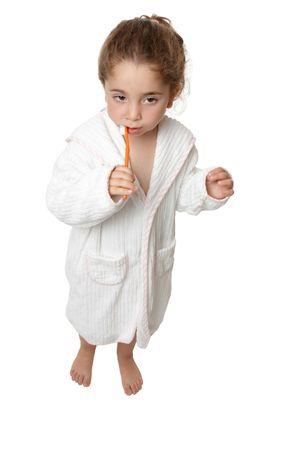 A small toddler girl in bathrobe is standing and brushing her teeth Stock Photo - 5214786