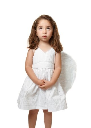 untroubled: Little angel girl wearing a beautiful white embroidered dress.  She has her hands gently clasped and is looking up toward heaven or sky