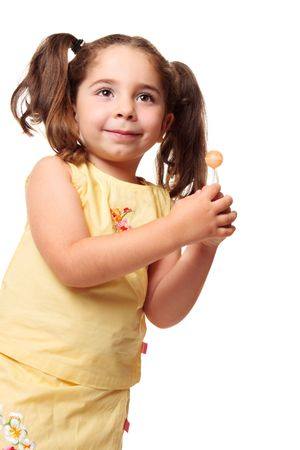 Little girl dressed in yellow is holding a sweet lolly Stock Photo - 5351519