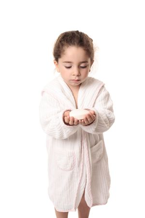 Little girl in white bathrobe holding a bar os soap in her hands. Stock Photo - 5351516