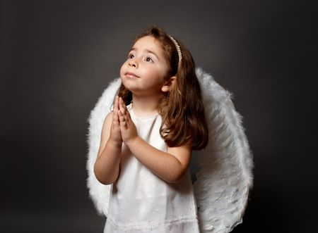 glorify: Little white angel child with hands together in devotional prayer and looking heavenward with hope and faith.