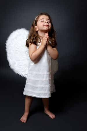 alas de angel: Angelito descalzo en vestido blanco y alas de plumas, con las manos unidas en oraci�n silenciosa Foto de archivo
