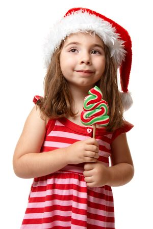 Little girl wearing a  red santa hat and striped dress.  She is holding a christmas tree lollipop candy on a stick photo