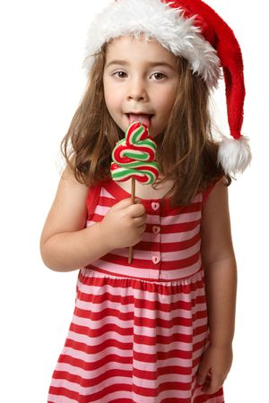 A preschooler wearing a red santa hat is holding a red, white and green christmas tree shaped lollipop candy and licking it Stock Photo - 5511007