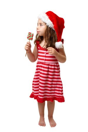 Christmas girl eating a lollipop candy in the shape of Christmas tree. Stock Photo - 5511004