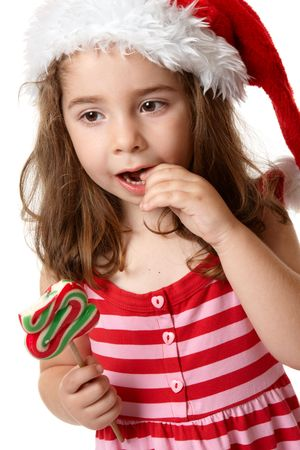 Young little girl eating a christmas tree candy Stock Photo - 5526945